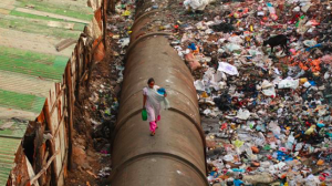 The effects of globalisation is often poverty. A woman walks on a pipe separating a row of houses and trash piles in India